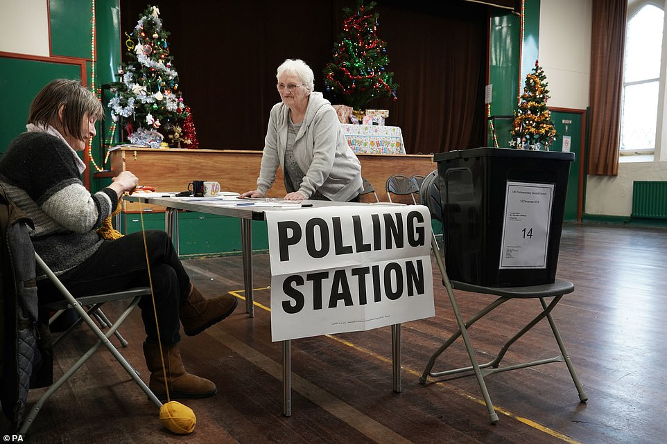 Chris Johnson (left), 62, does her knitting as she talks with colleague Christine Habberjam, 72, while awaiting people to vote at the polling station in Nenthead Village Hall in Cumbria