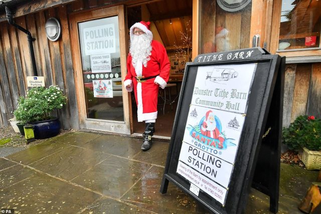 A man dressed as Father Christmas walks from his grotto to vote at the Dunster Tithe Barn near Minehead, Somerse