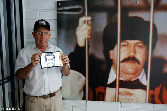 New images of a smartphone designed by the brother of an infamous Colombian drug lord set to take on Apple have emerged. Pictured is that smartphone creator Roberto Escobar standing next to a photo of his deceased brother, Pablo Escobar