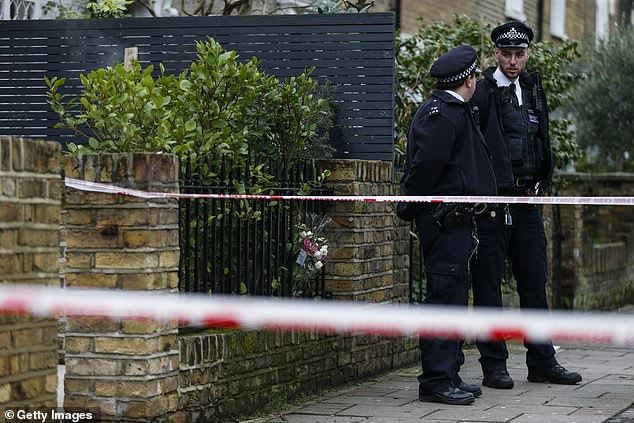 Officers stand outside the house where Mr Beqiri was shot to death on Christmas Eve