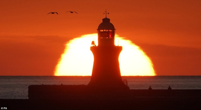 People heading to watch the Mayor of London 's annual fireworks display in the capital will face temperatures of about 6C (42.8F), while revellers in Edinburgh and Glasgow can expect the mercury to dip to about 2C (35.6F). Pictured: South Shields lighthouse on the north east coast as the sun rose this morning