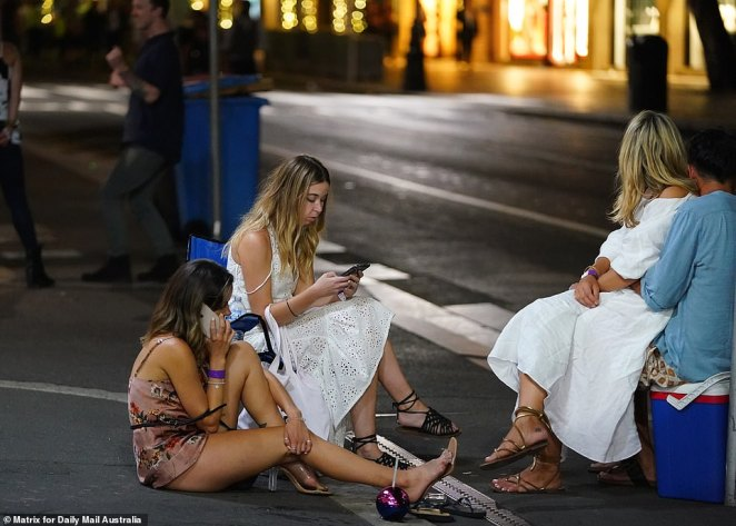 A group of women in summery dresses wait on a corner for their ride home to arrive. A couple use an esky as a seat as they wait