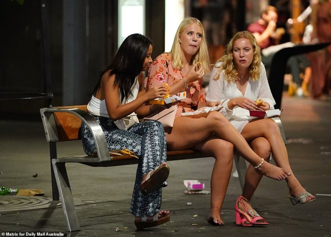 A group of glammed-up women end their night eating McDonald's in the street. A woman in a peach dress was sick of wearing her shoes and opted to go barefoot for the rest of her meal