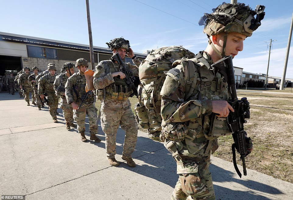 Army paratroopers march out to their C-17 transport aircraft as they leave Fort Bragg, North Carolina on Wednesday