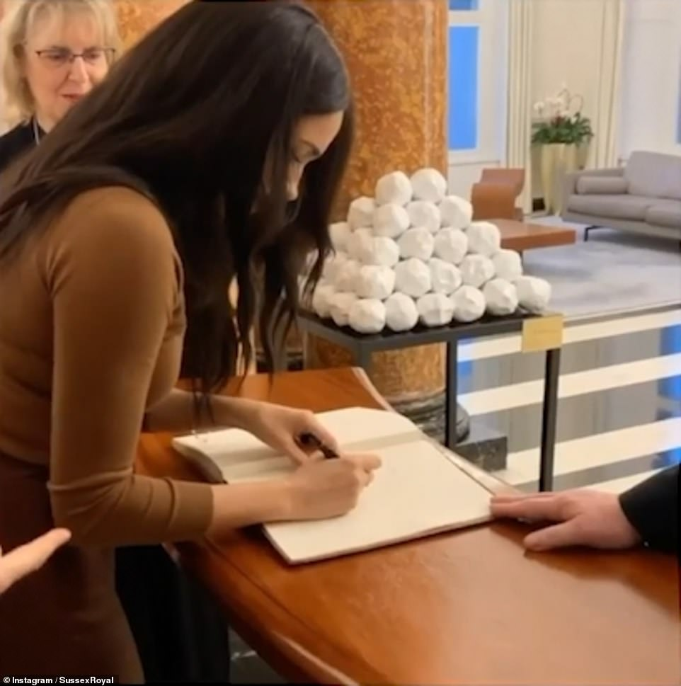 Meghan signing a guestbook at Canada House. The couple both appeared to be refreshed and in high spirits following their break