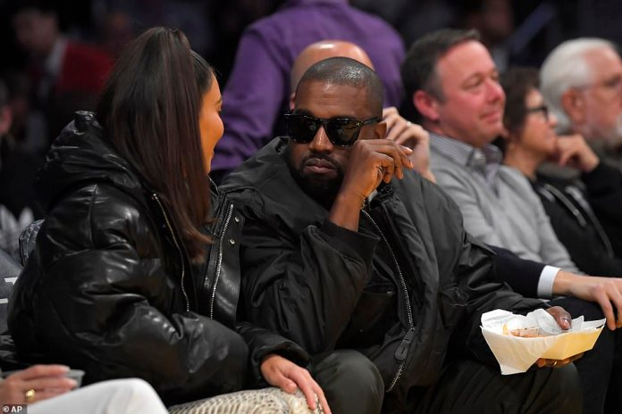 Snacking: Kanye chowed down on some snacks from the concession stand, tucking into some fries