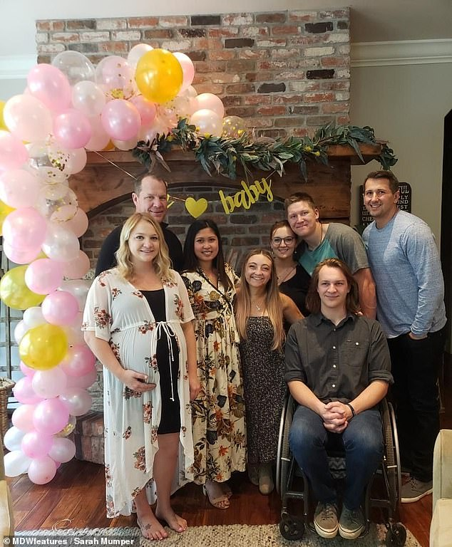 Sarah made the transition to her wheelchair slowly, even though for years something as simple as walking up the stairs could dislocate her joints. Pictured: with her family and boyfriend