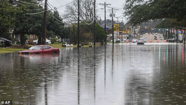 A woman sits stranded in her Dodge Charger on a flooded street in West Jackson, Mississippi on Tuesday