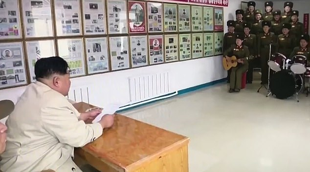 Spectator: North Korean strongman Kim Jong-un sits behind a desk and watches the performance by women in military uniform