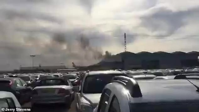 A view from the parking lot shows the dense smoke that rises from the Alicante airport building today
