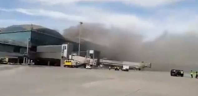 Smoke can be seen waving from the roof of the Alicante airport after a fire started today in the terminal building