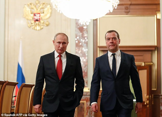 Russian President Vladimir Putin and Prime Minister Dmitry Medvedev walk before a meeting with members of the government in Moscow on Wednesday. Medvedev announced his resignation after Putin announced a raft of sweeping changes