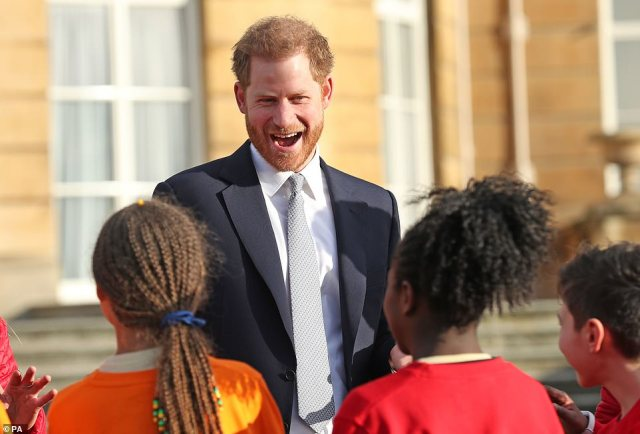 Harry's face lights up as he meets local children in the Buckingham Palace gardens as he hosts the Rugby League World Cup 2021 draws at his grandmother's house