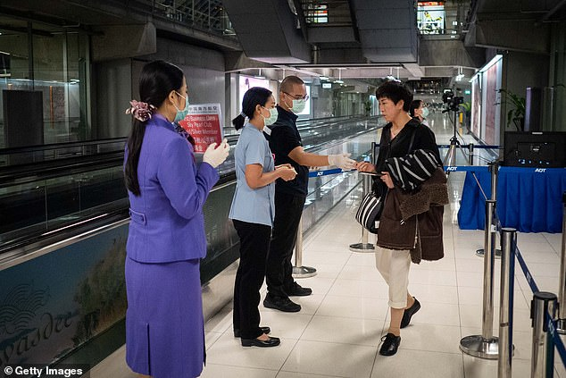 Countries in Asia, including Japan, Thailand and Singapore, have stepped-up surveillance at airports. Pictured, Bangkok airport staff performing thermal scans on a traveller