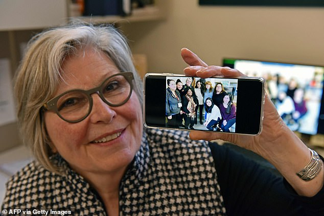 Kate Gibson, Acting Executive Director Downtown Eastside Women's Centre, shows a photo of staffers posing with Meghan Markle.'It would have been a way bigger deal for her to have actually met our clients in a trip to the center,' she said, citing security issues that complicated Meghan meeting the at-risk women served there
