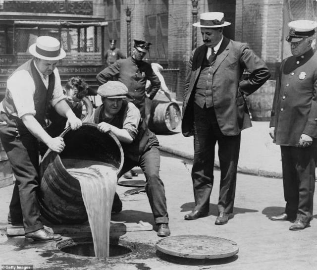 The 18th Amendment, which banned the nationwide manufacturing and sale of alcohol went into effect on January 17, 1920. New York City Deputy Police Commissioner, John A Leach (right) watches agents pour liquor into the sewer following a raid during the height of Prohibition in 1921.