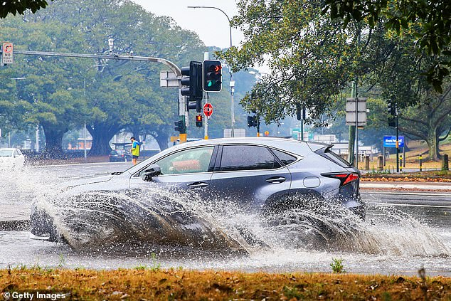 Heavy rains tested Sydney's stormwater drains on Friday morning. Pictured is a car driving through a giant puddle in the inner-city suburb of Surry Hills