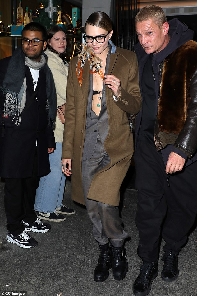 Funky:The model, 27, teamed the co-ords with a brown overcoat, along with a bizarre accessory of colourful feathers