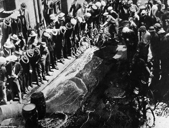 Contraband beer being spilled into the streets from barrels during the Prohibition era.