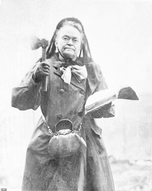 Carrie Nation, an outspoken temperance leader is pictured wielding her hatchet and bible in 1910. Nation became a household name after vandalizing multiple saloons with her ax. She described herself as 'a bulldog running along at the feet of Jesus, barking at what He doesn't like' and said that she was divinely ordered to advocate for temperance by destroying bars.