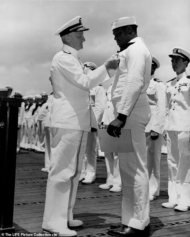 Admiral Chester W. Nimitz, the commander in chief of the Pacific Fleet (left) presents the Navy Cross to Miller (right) in Pearl Harbor in May 1942. Miller was the first African American to receive the Navy Cross for valor