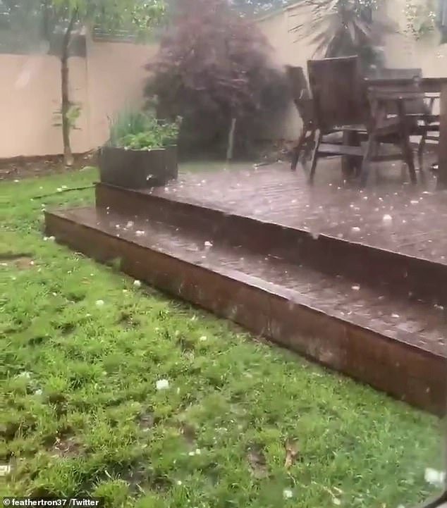 Residents were forced to take shelter as the massive hailstones battered their properties as the rainfall began to get heavier (pictured)