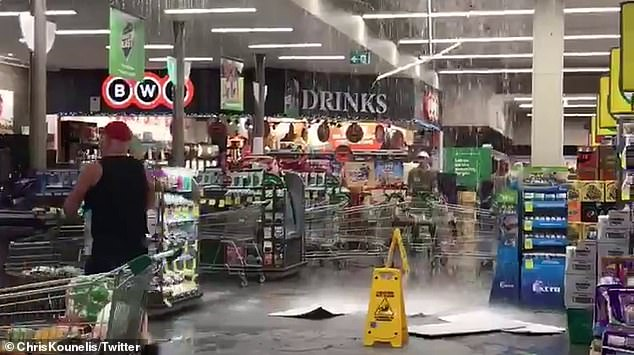 A severe thunderstorm warning has been issued for large areas of Victoria as heavy rainfall and 'giant hailstones' begin to batter the state with one Woolworths being inundated (pictured)