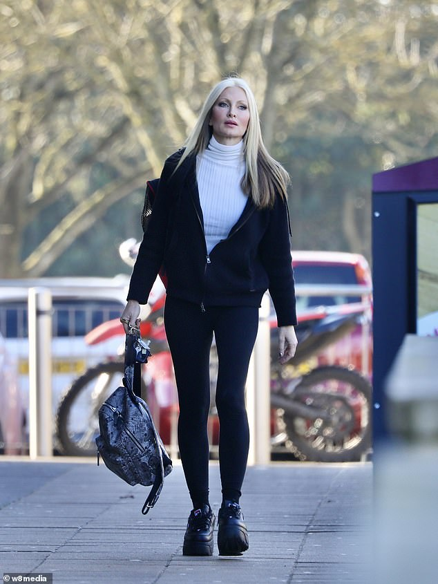 Stylish: She wore a black tracksuit top layered over a white polo neck