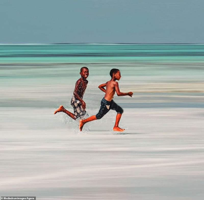 This sweet snap of two boys running on the beach is titled 'Friends Playing' and was shot in Tanzania by a British photographer known as @sollylevi