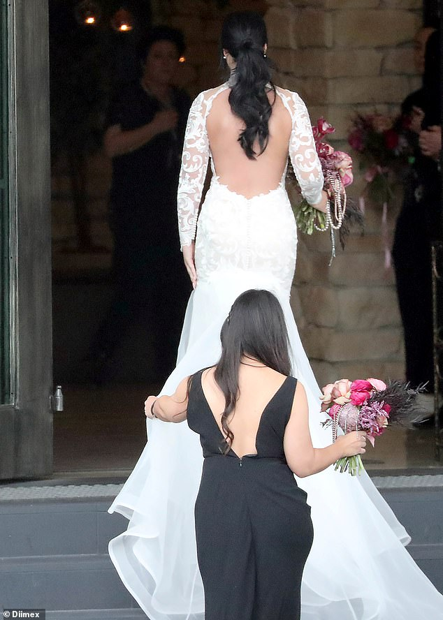 Details: Her backless gown featured intricate detailing throughout and a high neck design