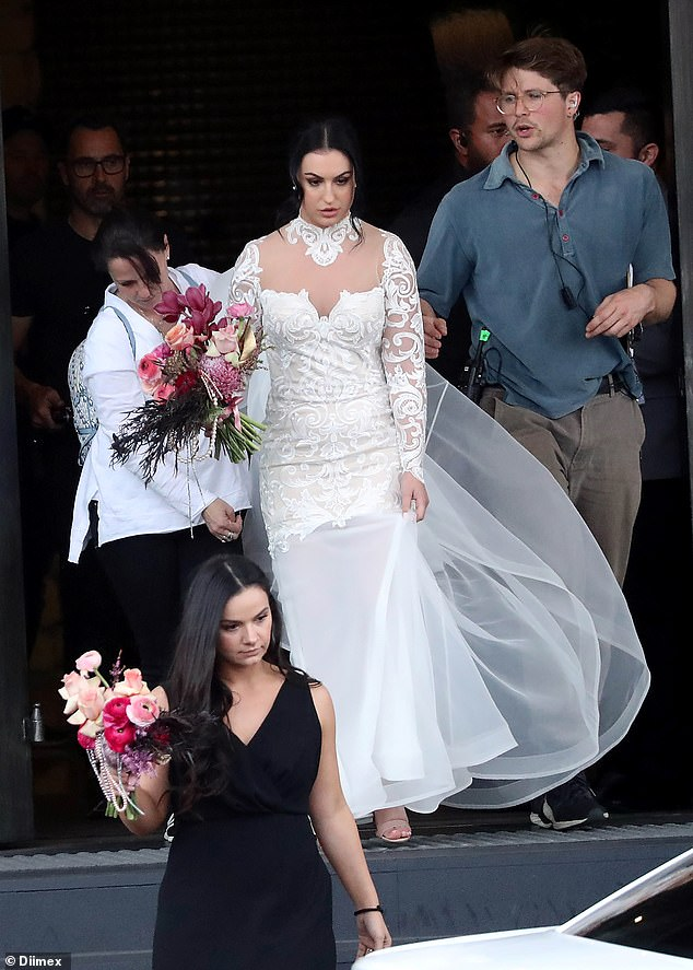 Helping hand: She clutched a bouquet of flowers and was followed by a female producer, who helped adjust her dress