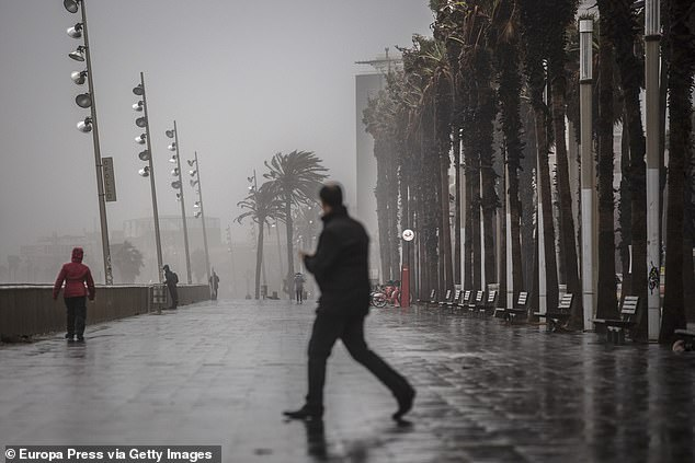 A man walks along the promenade of Barcelona where the 'Gloria' storm has left strong gusts of wind and rain