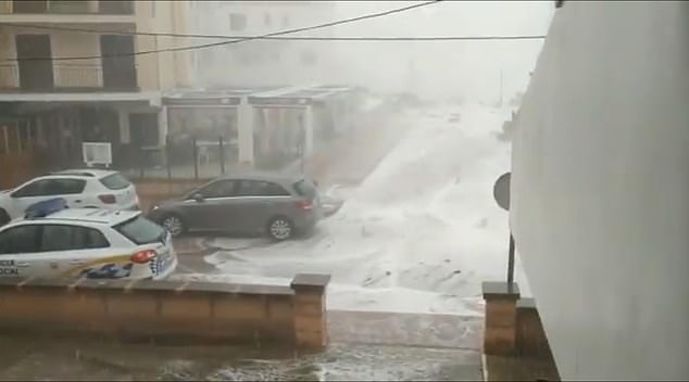 Mallorca is smashed by huge waves Tuesday with water seen rushing through the street towards buildings