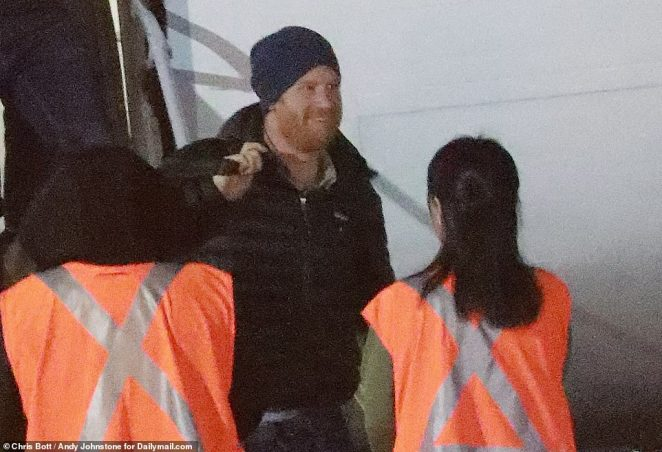 Prince Harry smiles after arriving on a WestJet plane at Victoria Airport on Vancouver Island in Canada on Monday night