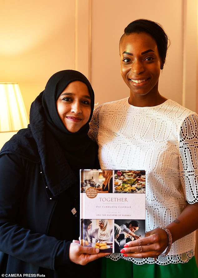 Zahira Ghaswala and Natalie Campbell (right) hold a copy of Together, a book that tells how women came together after the Grenfell Tower tragedy to cook for the local community, which has a foreword by the Duchess of Sussex