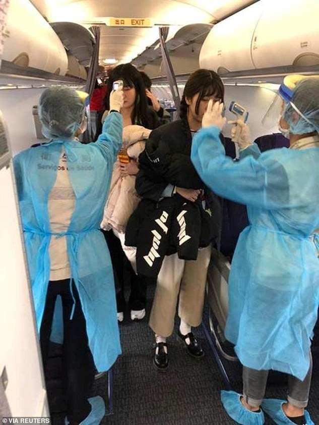 Officials measure temperatures of passengers on board on an Air China flight from Wuhan to Macau earlier this month