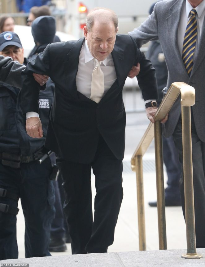 Weinstein climbs the stairs toManhattan Criminal Court on Thursday.The court was told Weinstein used his close friendship with Bill and Hillary Clinton to 'intimidate' his victim and prosecutors showed the jury a picture of Weinstein with Bill