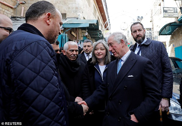 Britain's Prince Charles shakes hands with people as he arrives to visit Omar mosque in Bethlehem in the Israeli-occupied West Bank of Palestine