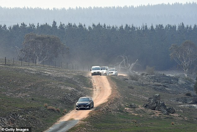 New South Wales forensic officers and a coronial van depart the crash site on January 24, 2020 in Peak View, Australia