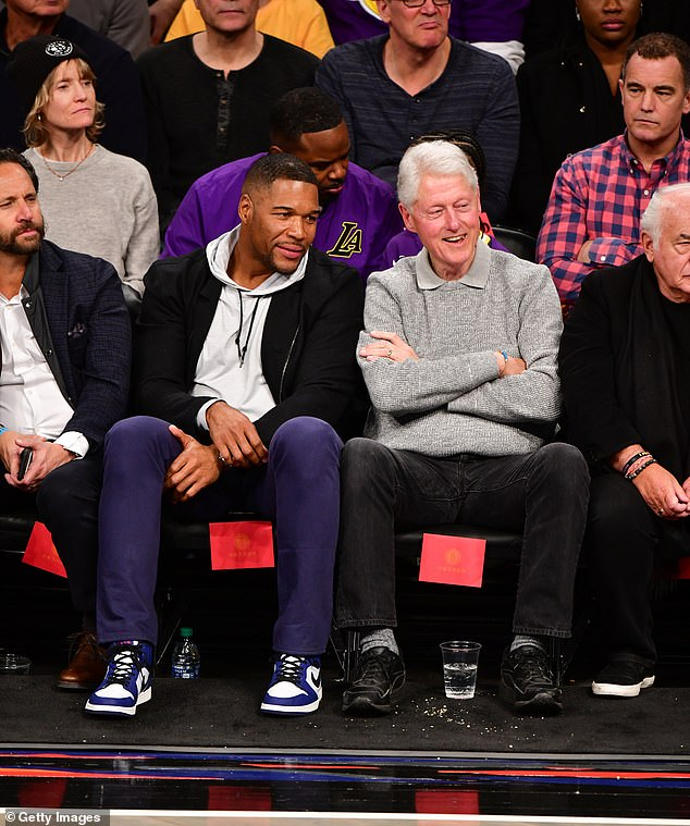 Bill Clinton, seen sitting sportside with Michael Strahan, can be seen looking intently at the court as the game is played