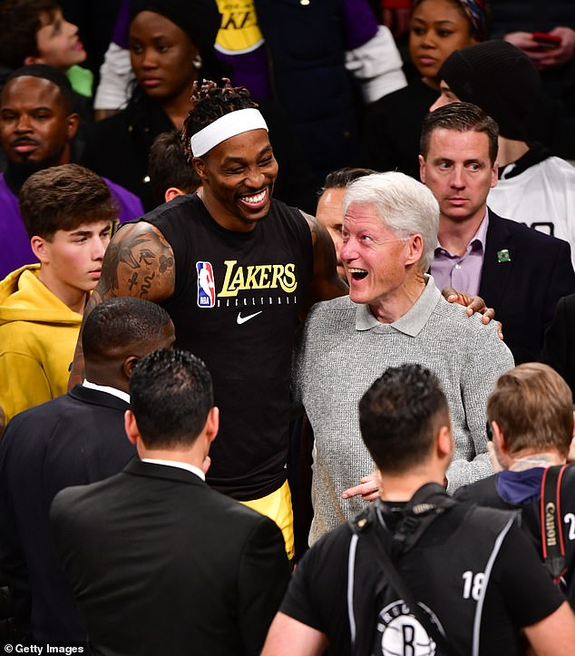Lakers player Dwight Howard and Bill Clinton appear to share a joke as they pose in front of the media