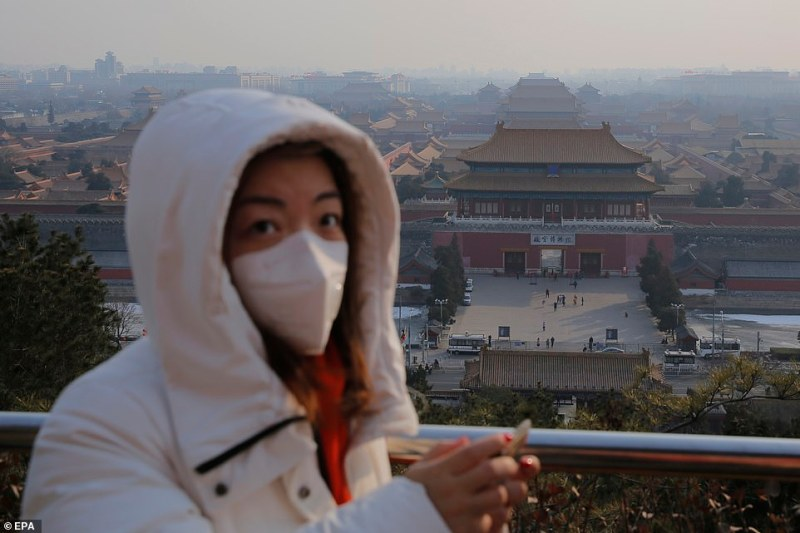 A woman is pictured wearing a mask in front of the now-closed Forbidden City in Beijing. The building houses the capital's Palace Museum but has been shut to visitors to stop the coronavirus spreading