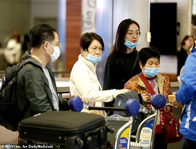 US health officials are testing 12 patients across the country for the new, mysterious coronavirus that has been spreading across the globe. Pictured: Travelers with masks at LAX