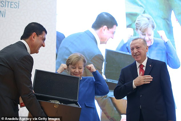 Angela Merkel is presented with the gift.Merkel arrived in Istanbul days after she hosted a meeting in Berlin on the conflict on Libya, where world powers pledged to halt foreign interference and honor a widely violated arms embargo