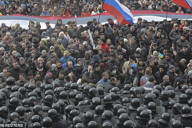 Kremlin analysts could have used Twitter as a source of military intelligence to inform their actions in the 2014 Russia–Ukraine conflict, a study has found. Pictured, pro-Russia protesters come face-to-face with riot police in front of a governmental building inKharkiv in 2014