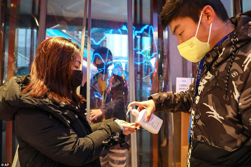 A worker dispenses hand sanitizer to a shopper at the entrance of a supermarket in Wuhan today as residents arrive to buy supplies amid the virus outbreak in the city
