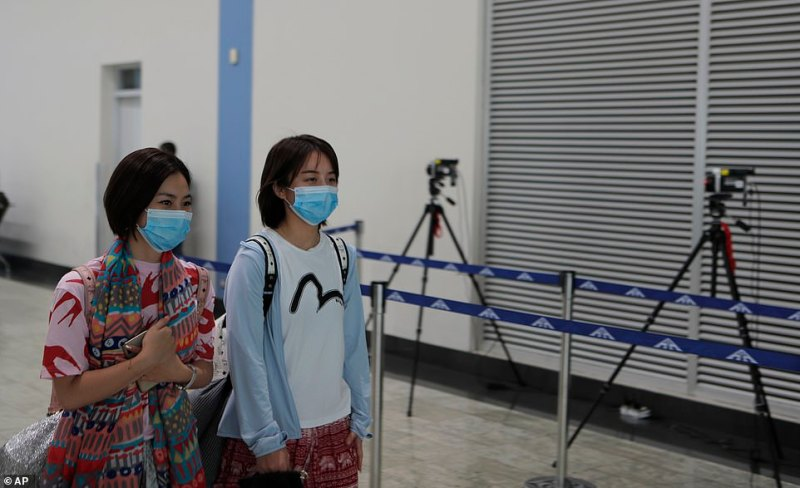 Chinese passengers wearing face masks walk past a thermal scanner set up to check the temperature of passengers at Colombo International airport in Colombo, Sri Lanka