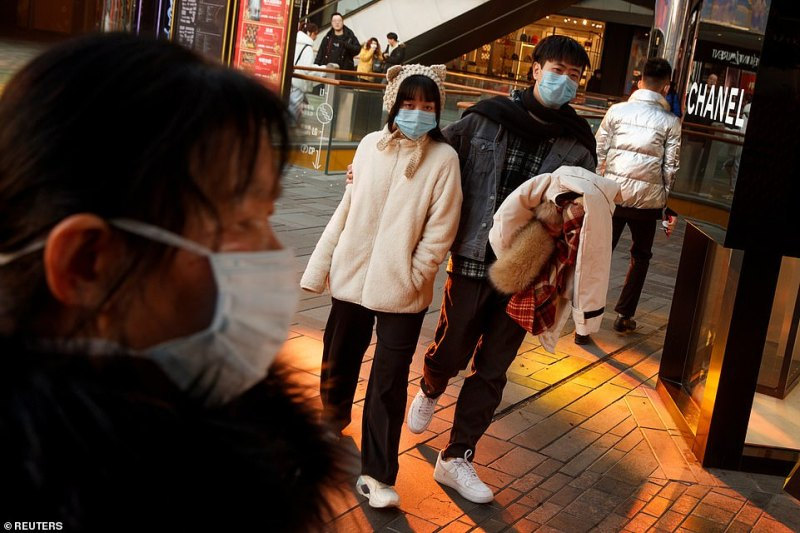 People wearing face masks walk past luxury boutiques in the Sanlitun shopping district in Beijing, China, as the country is hit by an outbreak of the new coronavirus today