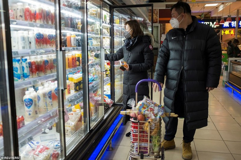 People wear face masks as they select products in a supermarket in Beijing, China amid coronavirus today