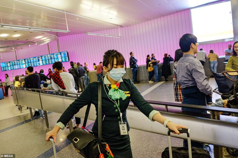 Screenings are also in place at Los Angeles International Airport. A staff member is seen wearing a face mask at LAX on Friday